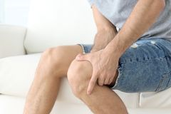 Young man suffering from leg pain. At home royalty free stock photo