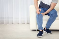 Young man suffering from leg pain indoors. Space for text. Young man suffering from leg pain indoors, closeup. Space for text royalty free stock image