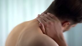 Young man suffering from neck pain, medical and healthcare concept, close up stock photo