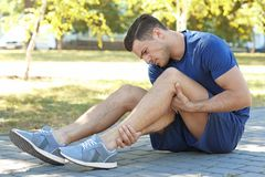 Young man suffering from pain in leg,. Outdoors royalty free stock photos