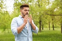 Young man suffering from seasonal allergy outdoors. Space for text royalty free stock photos