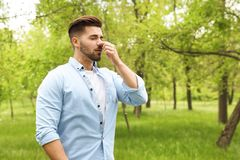 Young man suffering from seasonal allergy outdoors. Space for text royalty free stock image