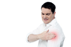 Young man suffering from shoulder pain. Middle aged man having shoulder joint pain Royalty Free Stock Images