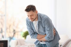 Young man suffering from stomach ache. At home royalty free stock images
