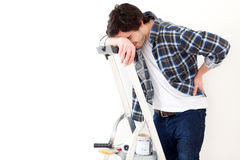 Young man suffering while working on a stepladder. View of a Young man suffering while working on a stepladder Stock Photography