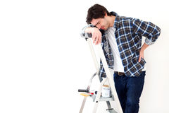 Young man suffering while working on a stepladder. View of a Young man suffering while working on a stepladder Royalty Free Stock Image