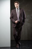 Young man in suit with banner for your text. Over grunge grey background Stock Images