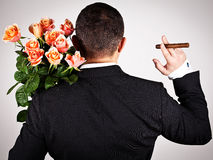 Young man in suit with bouquet of roses. Man wearing black suit hiding a bouquet of flowers behind his back. Valentines day Stock Image