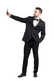 Young man in suit with bow tie taking selfie with cellphone Stock Images