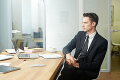 Financial analyst. Young man in suit brainstorming by his workplace in office royalty free stock image
