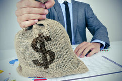 Young man in suit with a burlap money bag with the US dollar sig Royalty Free Stock Photos