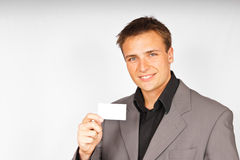 Young man in suit with business card Royalty Free Stock Images