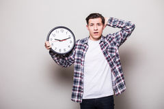 Young man in suit with clock in hands miss something Stock Photo
