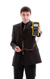 Young man in a suit demonstrates a multimeter. Stock Images