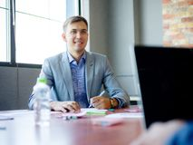 Young man in suit, at desk in office. Close-up of a bottle of water. Royalty Free Stock Photography