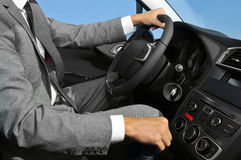 Young man in suit driving a car Stock Photo