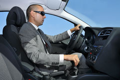 Young man in suit driving a car Stock Photos
