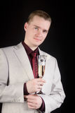 Young man in a suit with a glass of champagne Stock Photography