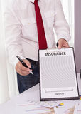 Young man in suit in his office showing an insurance policy and Stock Photo