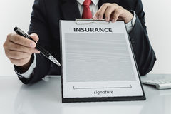 Young man in suit in his office showing an insurance policy and Stock Images
