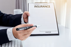 Young man in suit in his office showing an insurance policy and. Pointing with a pen where the policyholder must to sign Royalty Free Stock Photo
