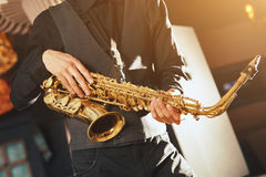 Young man in a suit hold saxophone Stock Photos