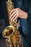 Young man in a suit hold saxophone Stock Photography