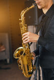 Young man in a suit hold saxophone Stock Images