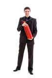 Young man in a suit holding a fire extinguisher. Young, smiling man in a suit holding a fire extinguisher, isolated on a white background Stock Image