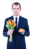 Young man in suit holding gift box with wedding ring and flowers Royalty Free Stock Images