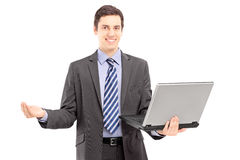 Young man in a suit holding a laptop and gesturing with hand Stock Photos
