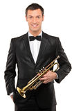 Young man in suit holding a trumpet Royalty Free Stock Photography