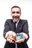 Young man in suit holding up win poker chips at game. Win poker Royalty Free Stock Photography