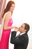 Young man in suit kissing hands of woman. Young man in suit kissing hands of red hair woman in evening dress stock photo