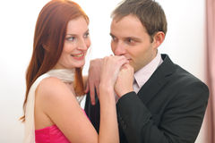 Young man in suit kissing hands of  woman. Young man in suit kissing hands of red hair woman in evening dress Stock Image