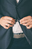 Young man in suit, lapel buttoning jacket, Close up Royalty Free Stock Photos