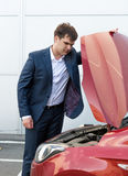 Young man in suit looking under the hood of broken car Royalty Free Stock Images