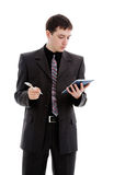 A young man in a suit, looks in a notebook. A young man in a suit, looks in a notebook, isolated on a white background Royalty Free Stock Photo