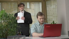 Young man in a suit makes a presentation to two employees of the office. He tells the story impulsively, gestures with. His hands. Work in the office concept stock video