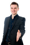 Young man in suit offering to shake the hand. Isolated on white background Stock Image