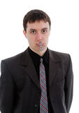 Young man in a suit, a pin with your mouth closed. Royalty Free Stock Images
