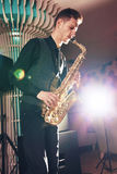 Young man in suit playing on saxophone Stock Photography