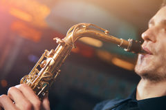 Young man in suit playing on saxophone. A young man in a suit playing on saxophone musical instrument Stock Images