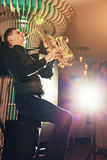 Young man in suit playing on saxophone. A young man in a suit playing on saxophone musical instrument Stock Photography