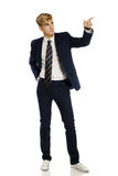 Young man in suit pointing to copy space Royalty Free Stock Photos
