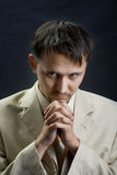 Young man in a suit, praying for something Stock Photos