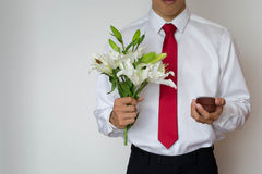 Young man in a suit proposing with an engagement ring and lilies. White litties. Man in white dress shirt and red tie Royalty Free Stock Photography