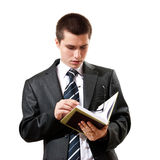 Young man in a suit reading a book Stock Photography