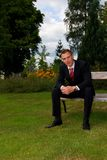 Young man in suit rest on the bench Stock Images