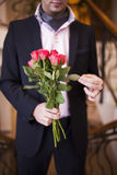 Young man in a suit with roses in their hands Stock Photography